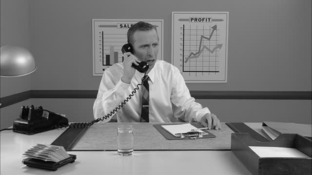 b/w ms businessman taking phone call and appearing shocked/ man crying and putting head down/ new york city - 2000s style点の映像素材/bロール