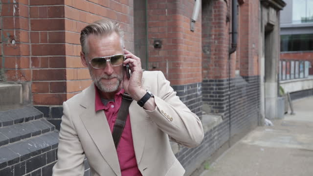 businessman taking phone call on the street, london - one mature man only stock videos & royalty-free footage