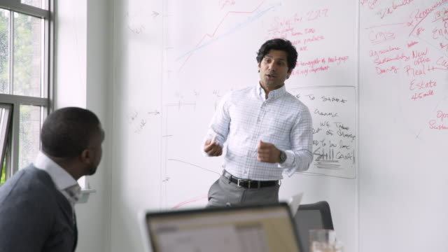 Businessman talking near whiteboard in meeting