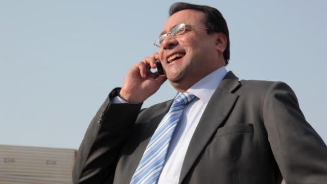 vidéos et rushes de businessman talking on a mobile phone and smiling, delhi, india - costume complet
