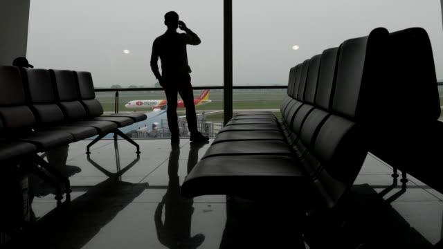 空港の窓口で携帯電話で話しているビジネスマン - 出張点の映像素材/bロール