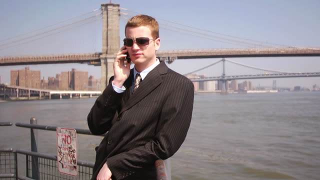 vídeos de stock, filmes e b-roll de businessman talking on cell phone by water - traje completo