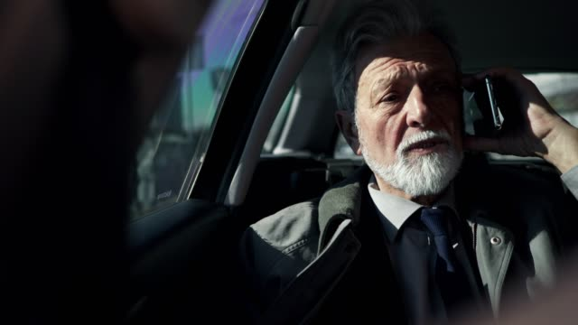 geschäftsmann spricht auf handy in einem auto - authority stock-videos und b-roll-filmmaterial