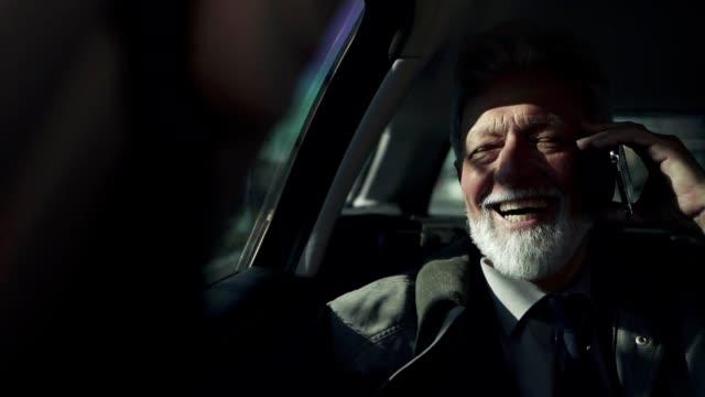 geschäftsmann spricht auf handy in einem auto - zufrieden stock-videos und b-roll-filmmaterial