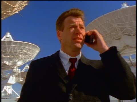 businessman talking on cellular phone in wind in front of vla radio telescope dishes / new mexico - suit stock videos and b-roll footage