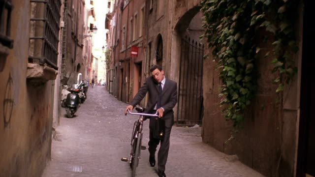 Businessman talking on cellular phone, pushing bicycle, + checking watch on narrow street / Rome