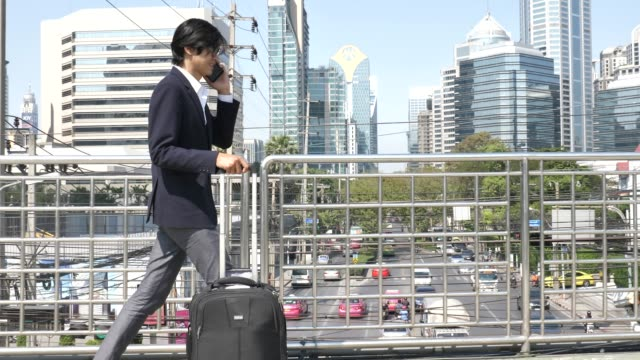 businessman talking on his phone, and pulling suitcase while commuting to work in city - equipment stock videos & royalty-free footage