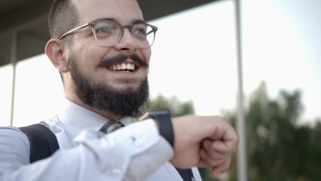 4k: affärsman talar på sin smarta klocka. - 30 34 ��r bildbanksvideor och videomaterial från bakom kulisserna