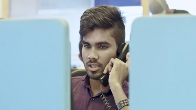 businessman talking on landline phone at office - indian ethnicity stock videos and b-roll footage