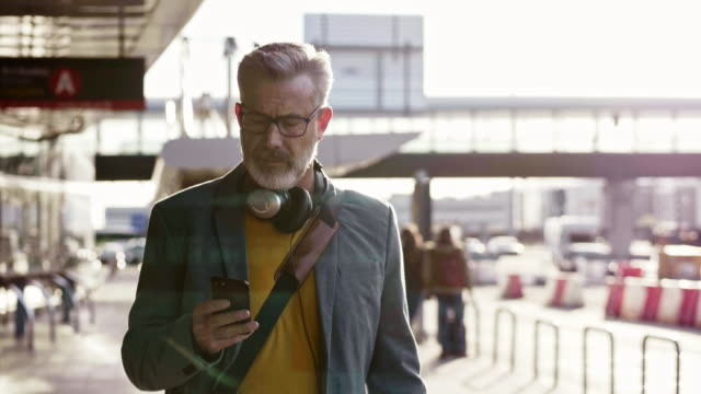 vídeos de stock e filmes b-roll de businessman talking on mobile phone at airport - 50 anos