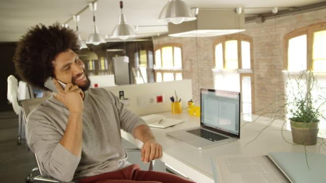 Businessman talking on mobile phone at desk. Shot on RED.
