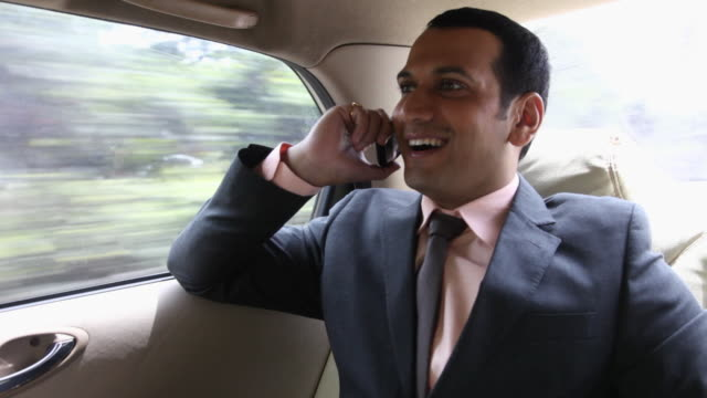 businessman talking on mobile phone in a car, mumbai, maharashtra, india - kompletter anzug stock-videos und b-roll-filmmaterial