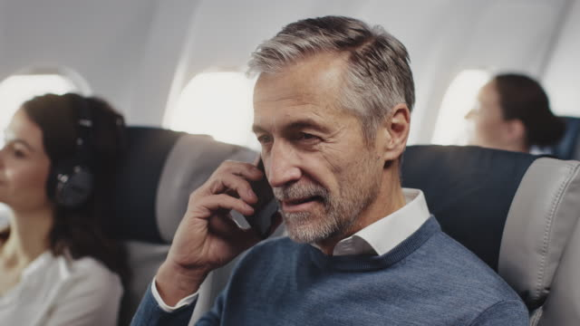 vídeos de stock e filmes b-roll de businessman talking on mobile phone in airplane - homens adultos