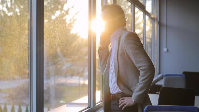 vidéos et rushes de homme d'affaires parlant sur le téléphone portable dans le bureau - seulement des jeunes hommes