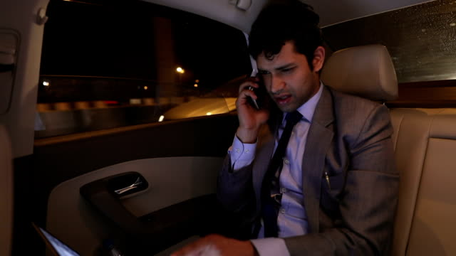 Businessman talking on mobile phone in the car, Delhi, India