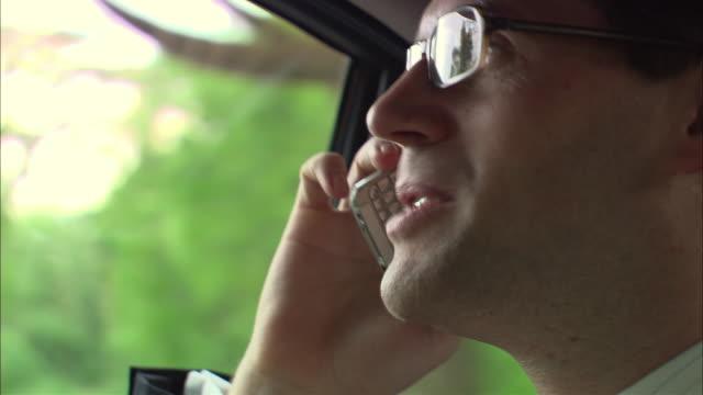 ECU, R/F, Businessman talking on mobile phone on car back seat, Singapore