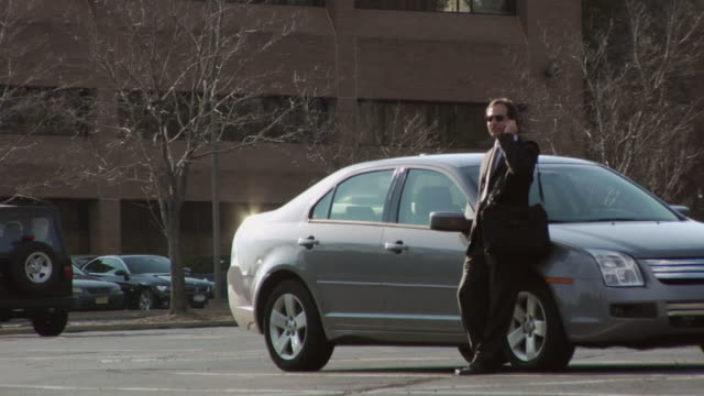 vidéos et rushes de ws, businessman talking on mobile phone on parking lot, upper saddle river, new jersey, usa - un seul homme
