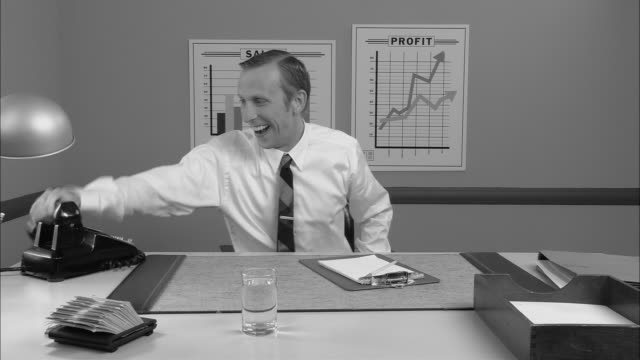 b/w ms businessman talking on phone and smiling as he receives good news/ man hanging up phone  smiling and giving thumbs up to camera  and leaning back in chair with feet up/ new york city - b rolle stock-videos und b-roll-filmmaterial
