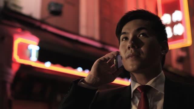 cu tu businessman talking on phone at night with neon signs in background / singapore - 全套西裝 個影片檔及 b 捲影像