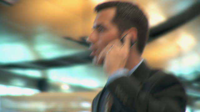 CU Businessman talking on phone, checking flight information in airport terminal, Appleton, Wisconsin, USA