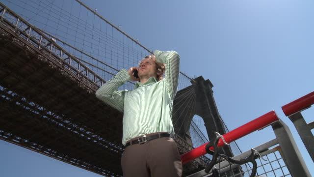 CU ZO LA MS Businessman talking on phone in front of Manhattan Bridge, New York City, New York, USA