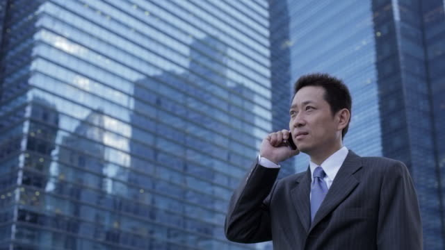 mh la ld businessman talking on phone in front of modern buildings / singapore - 前にいる点の映像素材/bロール