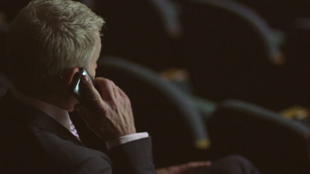 CU Businessman talking on phone in theater / South Orange, New Jersey, USA