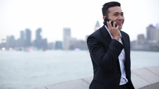 MS businessman talking on phone on The Bund, Shanghai