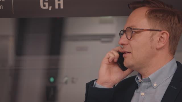 geschäftsmann spricht auf smartphone im zug - großunternehmen stock-videos und b-roll-filmmaterial