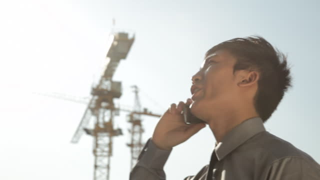 pan cu la businessman talking on the mobile phone with cranes in background / beijing, china - east asia stock videos & royalty-free footage