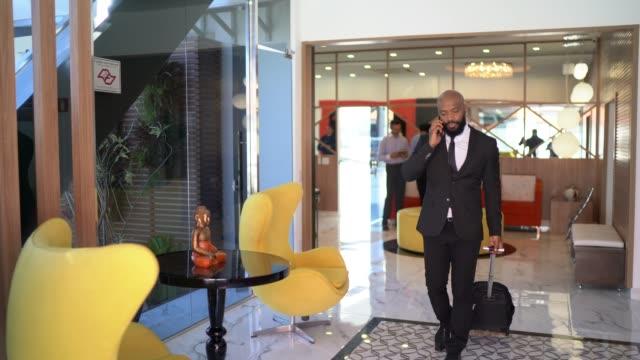 vídeos de stock, filmes e b-roll de homem de negócios que fala no telefone e que carreg a bagagem na sala vip do aeroporto - área de embarque de aeroporto