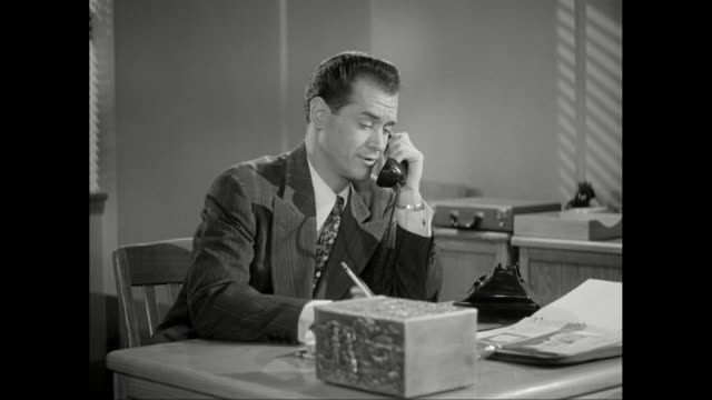 ms businessman talking on the phone in office / united states - 1950年点の映像素材/bロール