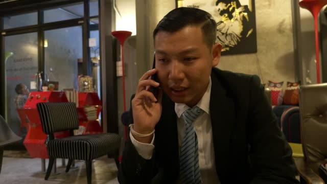 vidéos et rushes de homme d'affaires parlant au téléphone - hot desking