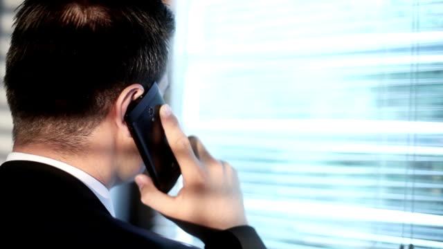 businessman talking on the phone - peeking stock videos & royalty-free footage