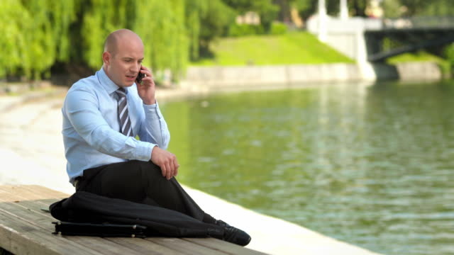 hd: businessman talking over phone in the city - completely bald stock videos and b-roll footage