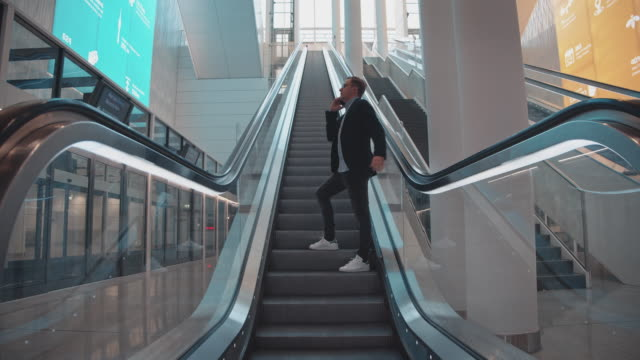 businessman talking through cellphone on escalator - escalator stock videos & royalty-free footage