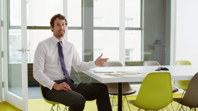MS Businessman talking to coworker while sitting at conference room table in office