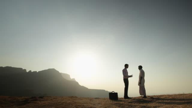 vídeos y material grabado en eventos de stock de businessman talking with a senior man on the cliff of mountain  - menos de diez segundos