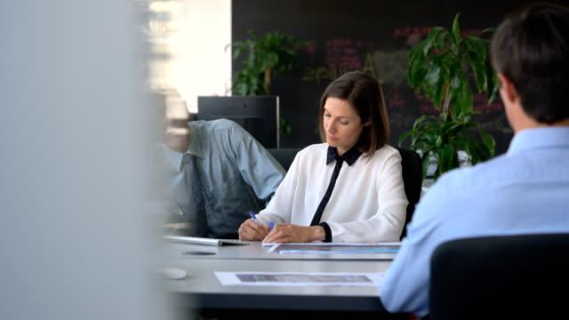 vídeos de stock e filmes b-roll de businessman talking with businesswoman in office - camisa e gravata