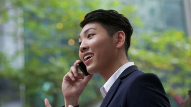 stockvideo's en b-roll-footage met businessman talking with phone in the street - oost azië