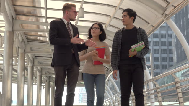 Businessman Talking With Two Students
