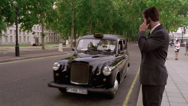 businessman talks on cell phone + hails taxi / black taxi stops + man gets in / london, england - taxi stock videos & royalty-free footage