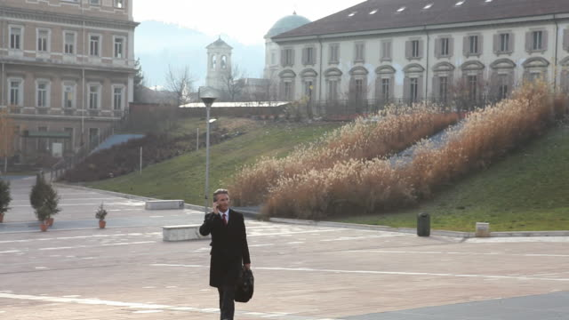 vídeos de stock, filmes e b-roll de businessman talks on cell phone, walks across piazza - só um adulto de idade mediana