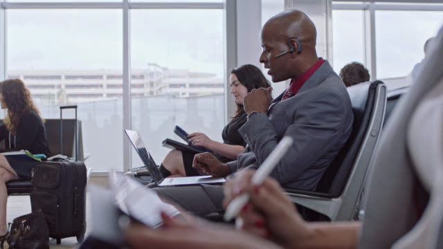 businessman talks on hands-free device amongst diverse business travelers at airport terminal gate. - bluetooth stock videos & royalty-free footage