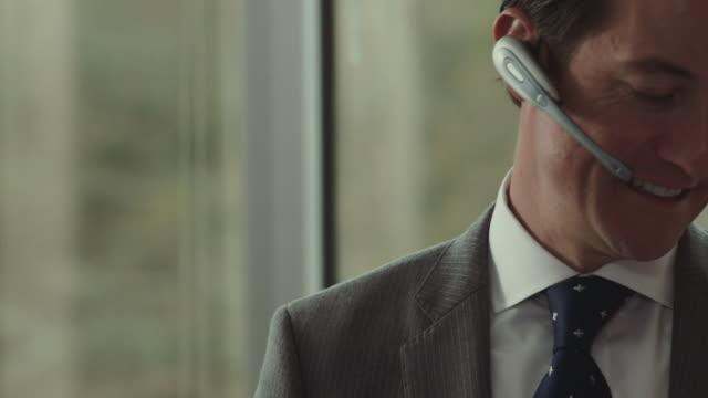 businessman talks on headset. - bluetooth stock videos & royalty-free footage