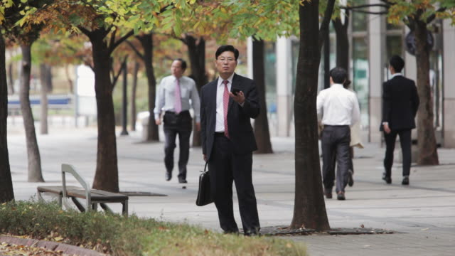 ls businessman talks on mobile phone in business district / seoul, south korea - south korea stock videos and b-roll footage