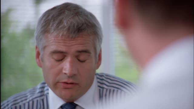 vidéos et rushes de a businessman talks to someone across from his desk. - profession supérieure ou intermédiaire