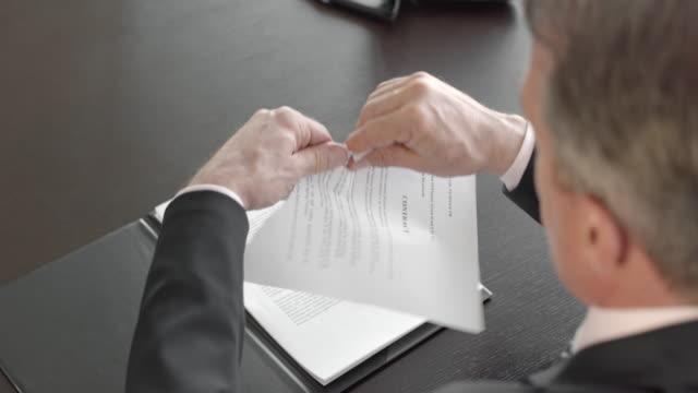 vídeos y material grabado en eventos de stock de hombre de negocios rompiendo un contrato en su oficina - contrato