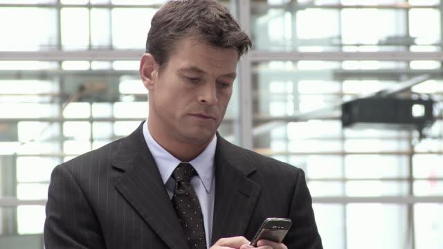 vídeos de stock e filmes b-roll de cu pan businessman text messaging in office building, copenhagen, denmark - fato completo