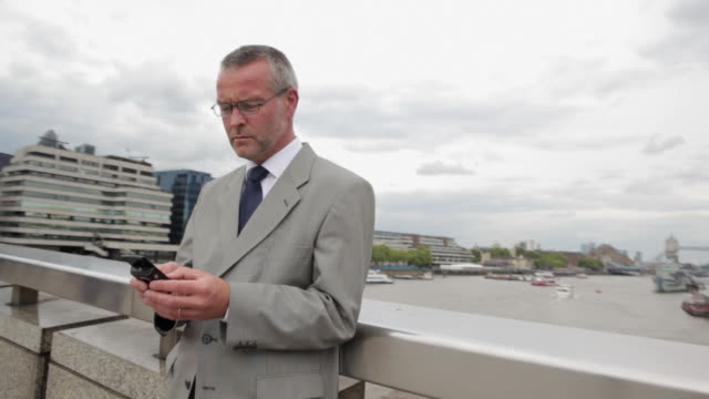 businessman text messaging on cellphone by river - file clerk stock videos & royalty-free footage